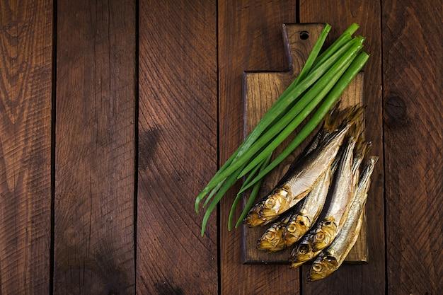 Sprat fumé et oignon vert sur une planche à découper sur un fond en bois. poisson fumé. vue de dessus Photo Premium