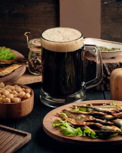 Sprat fumé, pois chiches bouillis servis avec une chope de bière Photo gratuit
