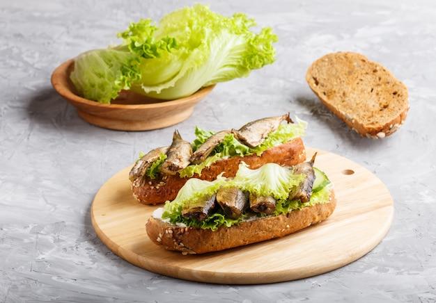 Sprats sandwiches avec laitue et fromage à la crème sur une planche de bois sur un béton gris. Photo Premium