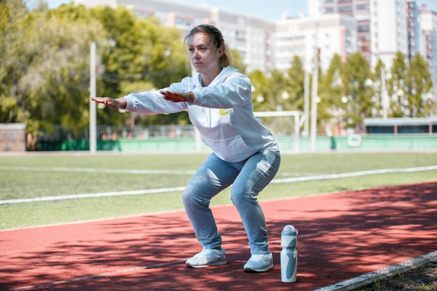 Squatting.young beauty girl faire des exercices au stade Photo Premium
