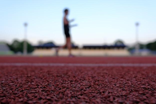Stade de plancher rouge pour la course et le jogging, exercice de personnes floues blackground. Photo Premium