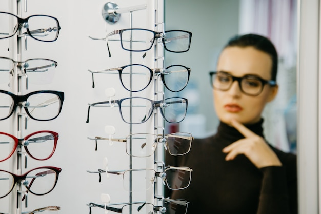 Stand avec des lunettes dans le magasin d'optique. Photo Premium