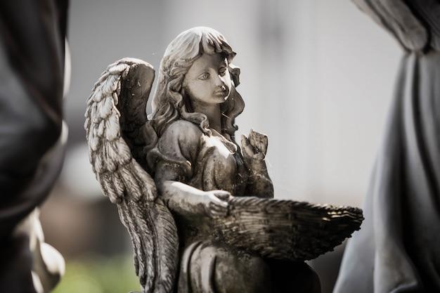 Statue d'un ange tenant un panier dans le jardin Photo Premium