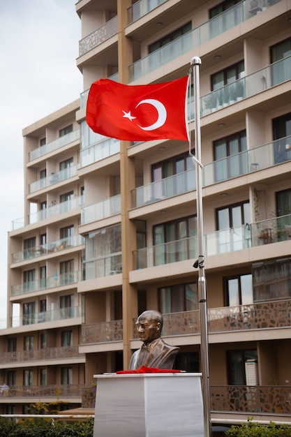 La Statue D'ataturk Et Les Drapeaux Turcs Devant Le Bâtiment Par Temps Nuageux. Concept De Symboles Turcs. Photo Premium