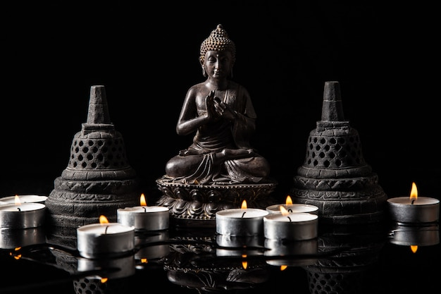 Statue De Bouddha Assis En Méditation, Avec Des Bougies Et Des Cloches Bouddhistes Photo Premium