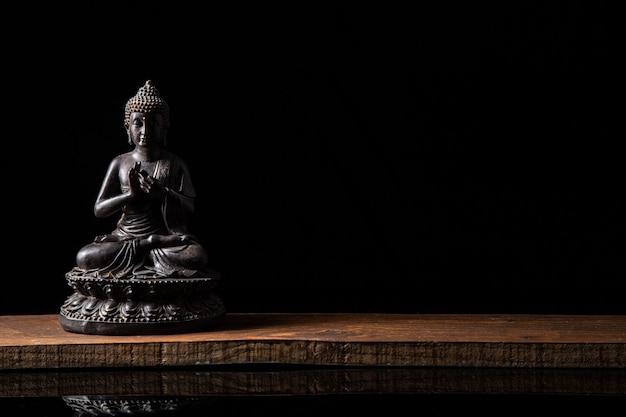 Statue De Bouddha Assis En Méditation Avec Espace De Copie Noir Photo Premium