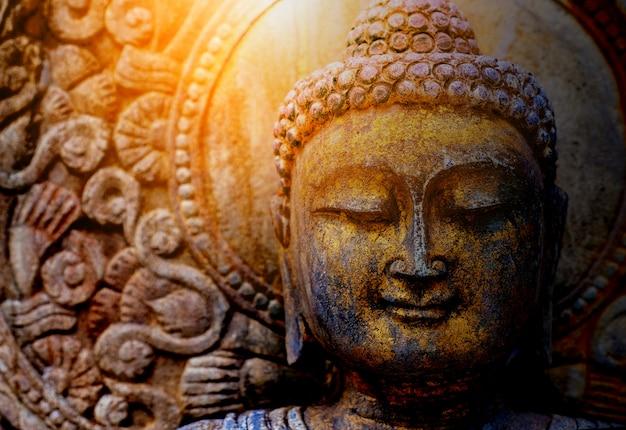 Statue de bouddha rock avec la lumière du soleil utilisée pour les amulettes de religion bouddhiste. Photo Premium