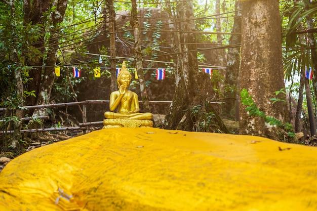Statue de bouddha en route vers la pierre avec l'empreinte du seigneur bouddha Photo Premium