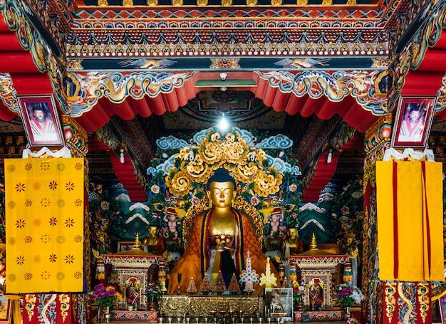 Statue de bouddha de style bhoutanais à l'intérieur du monastère royal bhoutanais décoré dans l'art bhoutanais à bodh gaya, bihar, inde. Photo Premium