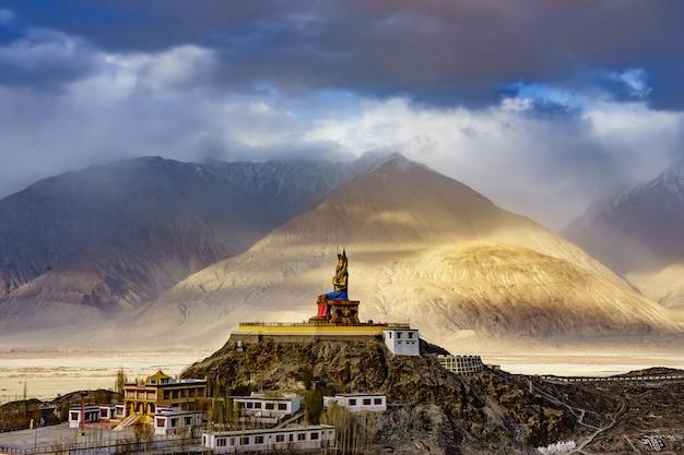 La Statue Du Bouddha Maitreya Avec Les Montagnes De L'himalaya à L'arrière-plan Du Monastère De Diskit Photo Premium