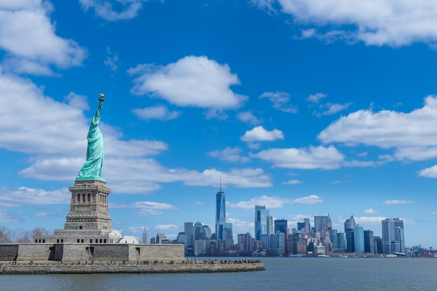 La statue de la liberté et de manhattan, new york city, etats-unis Photo Premium