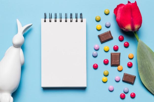 Statue de pâques blanches; bloc-notes en spirale; tulipe; bonbons gem et morceaux de chocolat sur fond bleu Photo gratuit