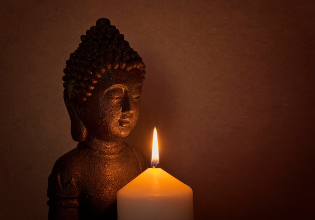 Statue d'un saint bouddha à la lumière d'une bougie Photo Premium