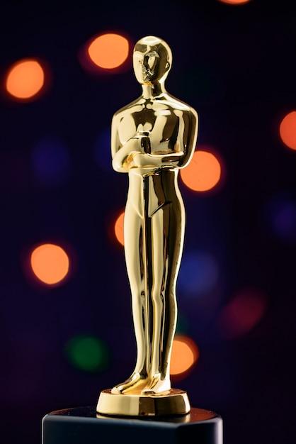 Statuette dorée complète sur les lumières défocalisés Photo Premium