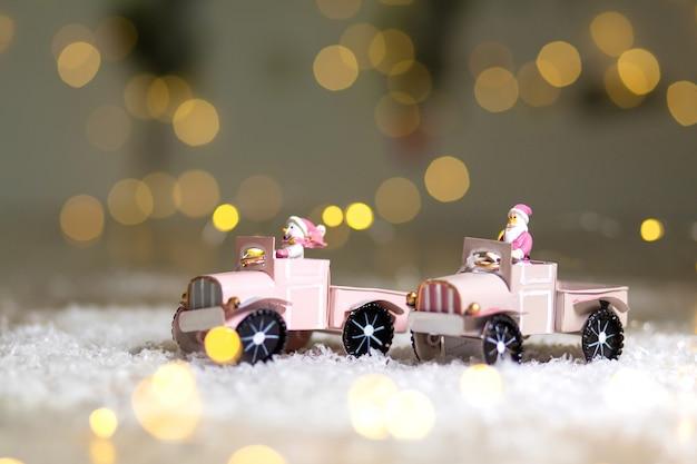 La statuette du père noël monte sur une voiture miniature avec une remorque pour cadeaux Photo Premium