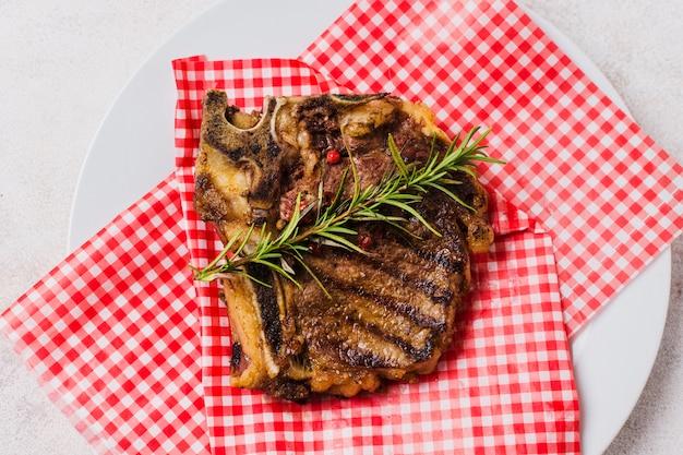 Steak sur assiette au romarin Photo gratuit