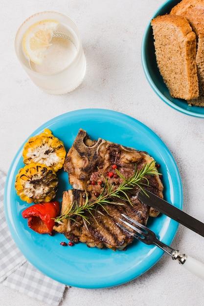 Steak sur assiette avec des légumes et des boissons Photo gratuit