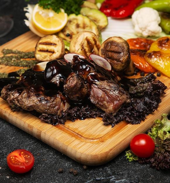 Steak de boeuf club avec sauce au poivre et légumes grillés sur une planche à découper Photo gratuit