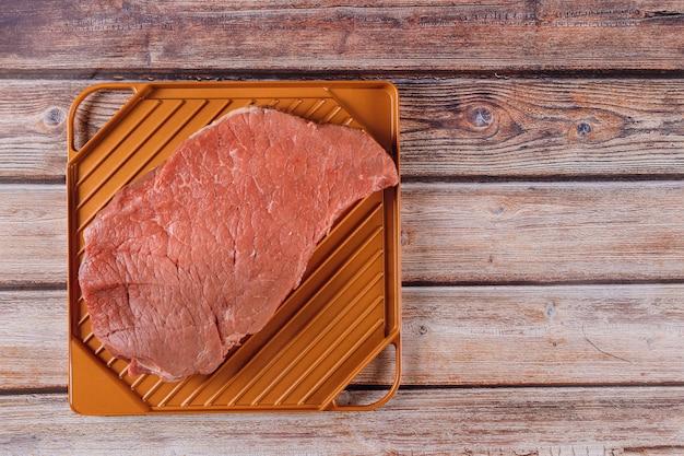 Steak de bœuf cru biologique sur une table en bois. Photo Premium