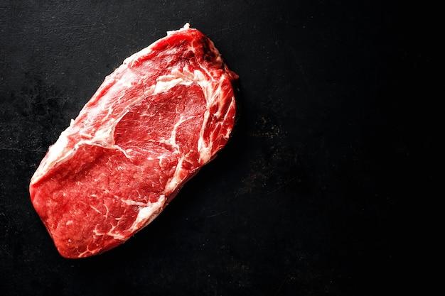 Steak de boeuf cru sur une surface sombre Photo gratuit