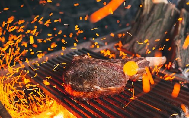 Le steak de boeuf est cuit sur le feu. bbq de côtes de boeuf. Photo Premium