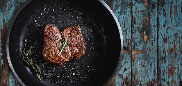 Steak De Boeuf Grillé Dans Une Poêle Sur La Texture Du Bois Photo Premium