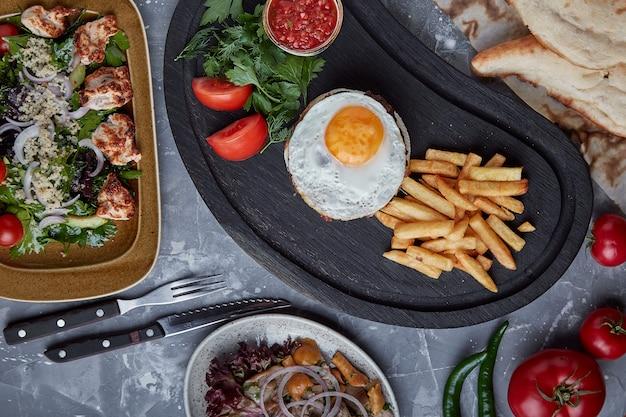 Steak de boeuf avec oeuf et salade de légumes verts et. fond en bois, réglage de la table, gastronomie Photo Premium