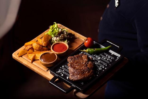 Steak de bœuf sur une plaque mini-grill avec pommes de terre frites, salade fraîche Photo gratuit