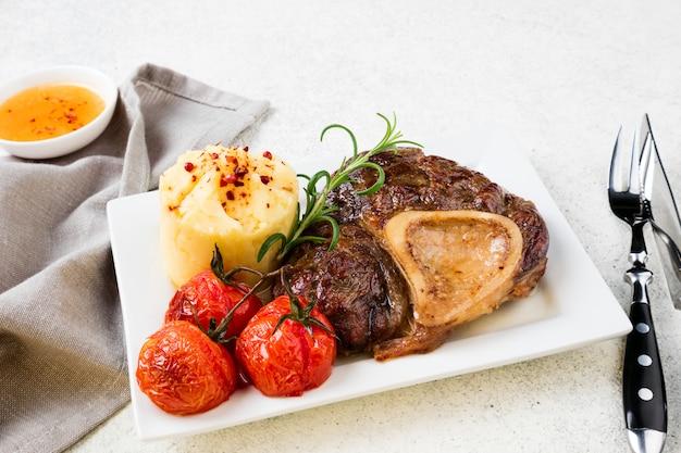 Steak De Boeuf Préparé Avec Osso Bucco Avec Purée De Pommes De Terre Et Tomates Photo Premium