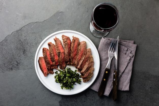 Steak de bœuf saignant sur assiette blanche, verre de vin rouge Photo Premium