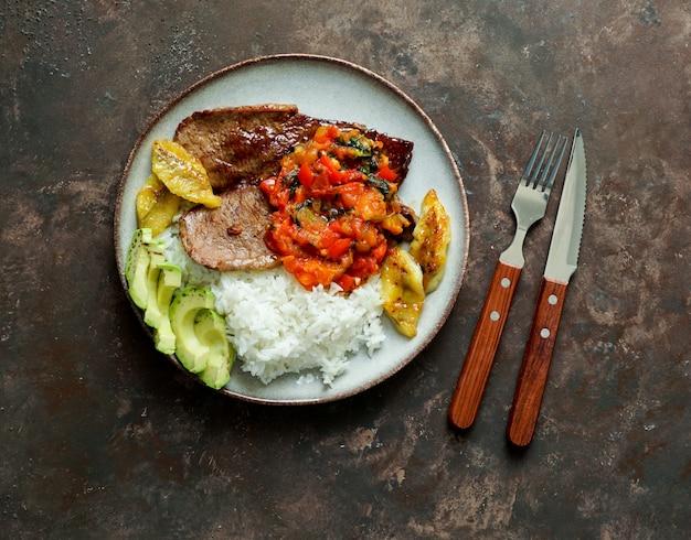 Steak de bœuf avec sauce tomates, riz, avocat et frites de bananes Photo Premium