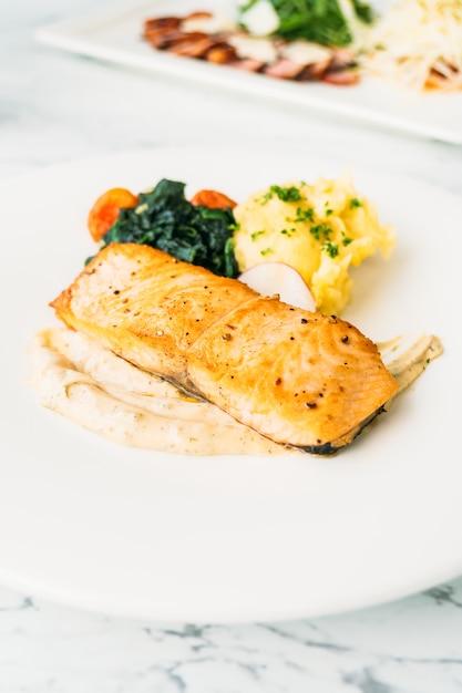 Steak de filet de viande de saumon grillé avec légumes et sauce Photo gratuit