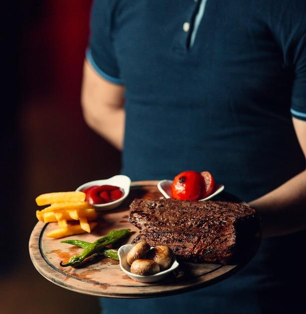 Steak frit avec des frites sur une planche de bois Photo gratuit