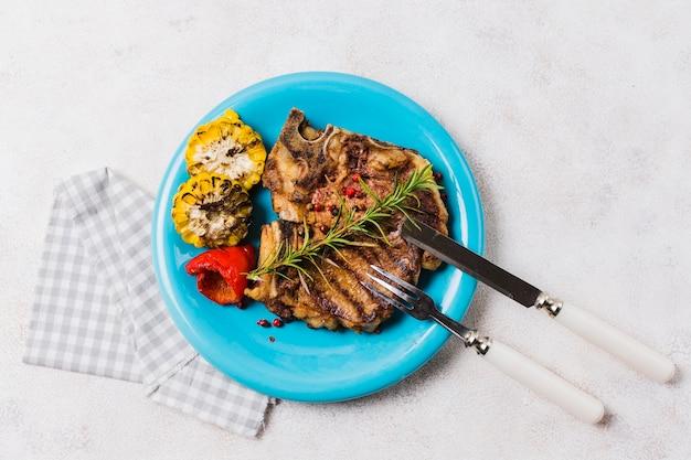 Steak avec des légumes sur une assiette avec des couverts Photo gratuit