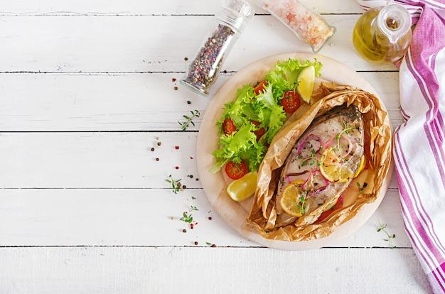 Steak de poisson blanc (carpe) cuit dans du papier sulfurisé avec des légumes. Photo Premium