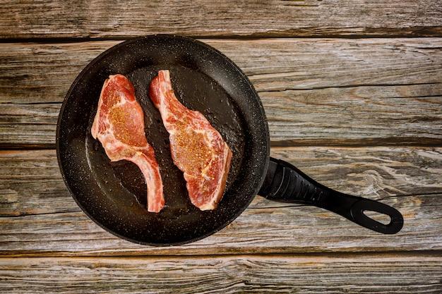 Steak De Porc Cru Sur Une Poêle En Fonte Sur Une Surface En Bois Photo Premium