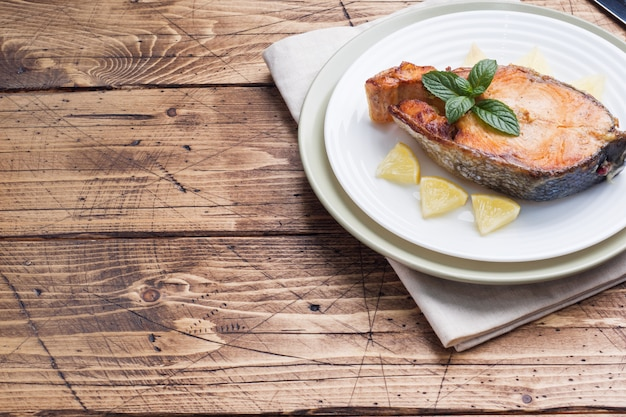 Steak De Saumon Au Poisson Sur Une Plaque Au Citron. Table En Bois. Photo Premium