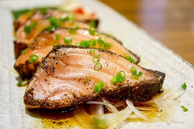 Steak de saumon au poivre noir et sauce dans une assiette blanche. Photo Premium