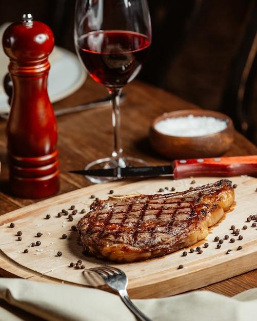 Steak soigné sur un support en bois avec un verre de vin rouge Photo gratuit