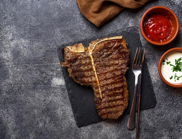 Steak de t-bone grillé sur noir Photo Premium