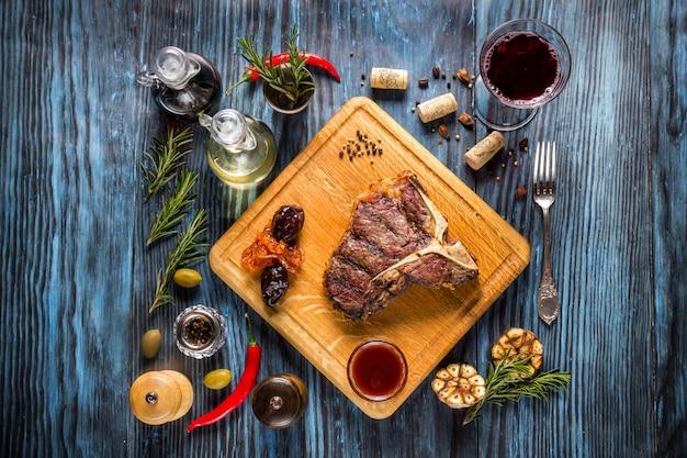 Steak de t-bone grillé, rare et rare, sur un fond en bois rustique avec romarin et épices Photo Premium