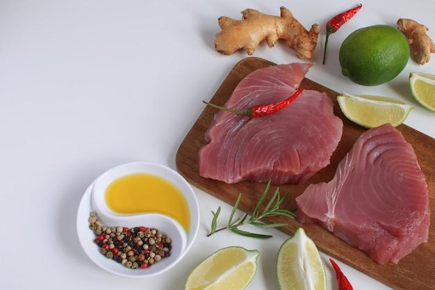 Steak de thon cru planche à découper en bois tranche de citron vert huile d'olive romarin racine de gingembre frais piment rouge Photo Premium