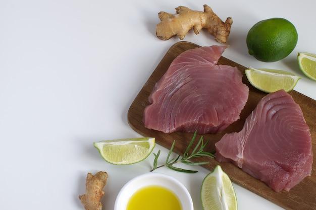 Steak de thon cru planche à découper en bois tranche de citron vert huile d'olive romarin racine de gingembre frais Photo Premium