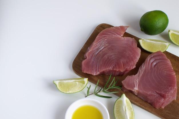 Steak de thon cru planche à découper en bois tranche de citron vert huile d'olive romarin Photo Premium