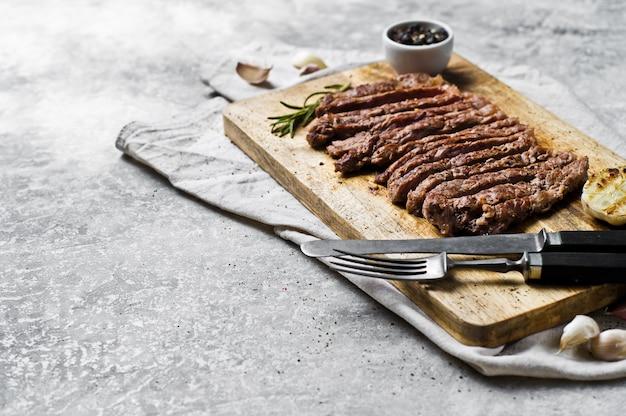 Steak tranché bbq sur planche à découper en bois. Photo Premium