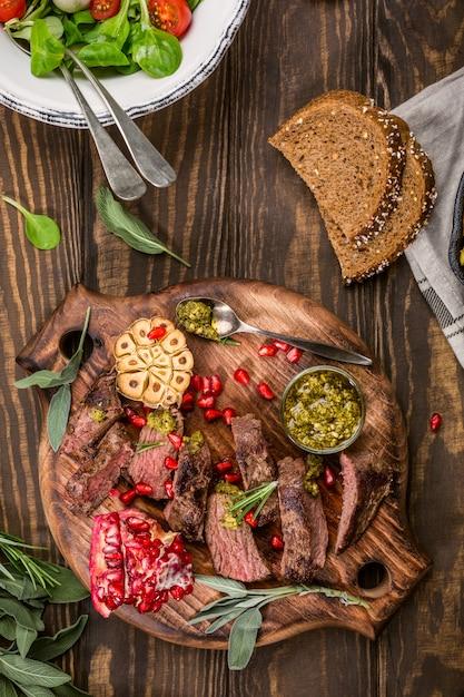 Steak de viande de kangourou au pesto vert et grenade sur une planche à découper en bois. Photo Premium