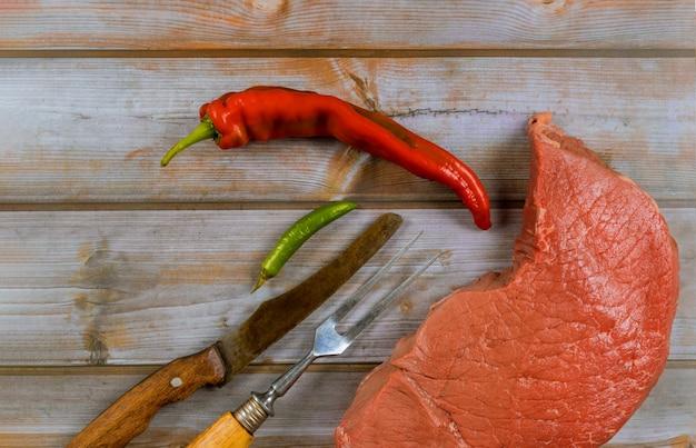 Steaks de bœuf cru frais avec couteau et poivron rouge sur fond en bois Photo Premium