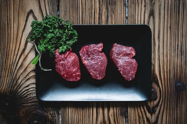 Steaks de boeuf cru sur une plaque noire Photo gratuit