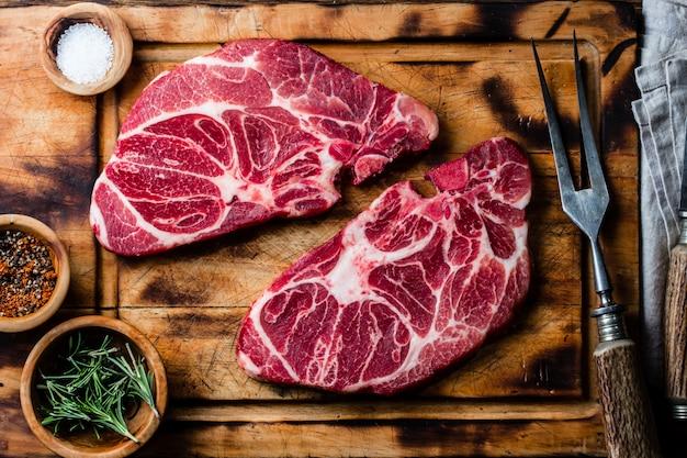 Steaks de boeuf marbrés crus sur une planche à découper en bois Photo Premium