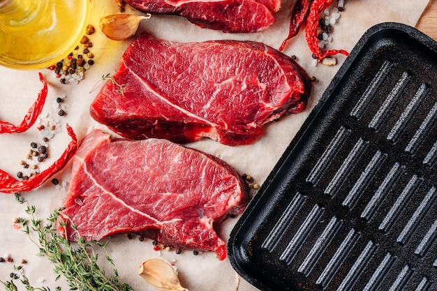 Steaks de boeuf à la viande prêts à être cuisinés avec de l'huile d'olive et des épices Photo Premium